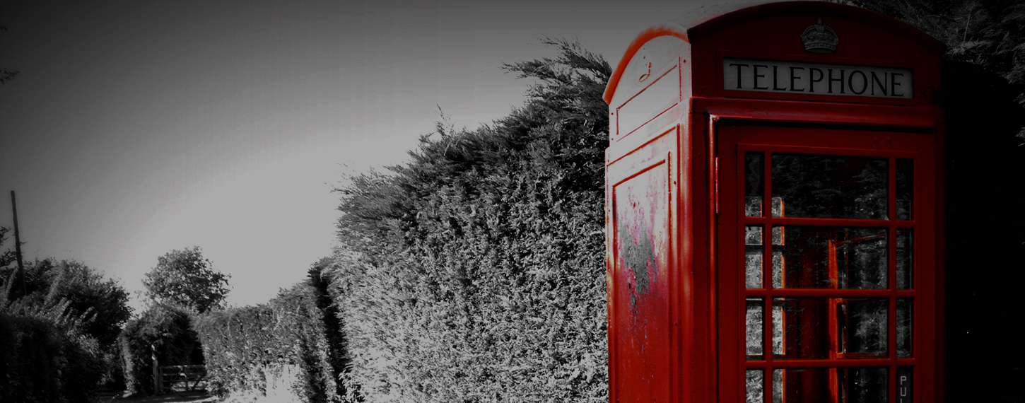 Red Telephone Boxes next to a wall